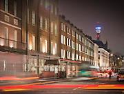 residential street at night in central london with car light rails and the BT tower in the Background
