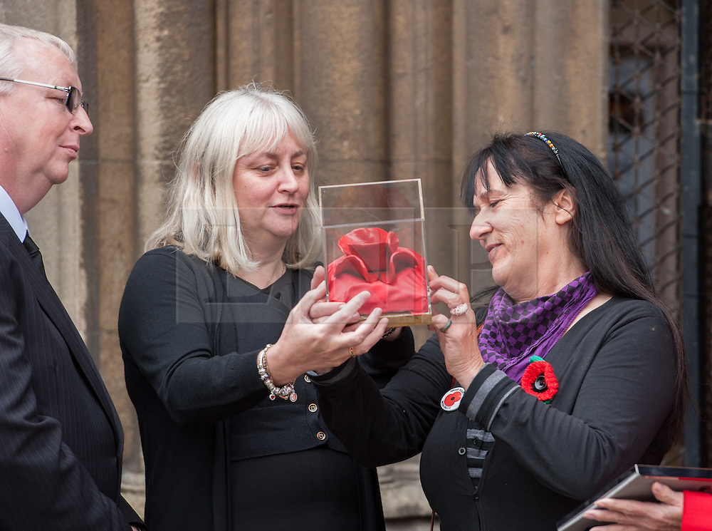 © Licensed to London News Pictures. 23/10/2015. Bristol, UK.  23/10/2015. Bristol, UK. Relatives of Bristol Poppy seller Olive Cooke at an event outside Bristol Cathedral, organised by the Royal British Legion, receive a ceramic poppy in memory of Olive from the Blood Swept Lands and Seas of Red exhibition.  L-R: John Hupfeld (Family friend), Linda Cooke (Olive's step grand-daughter-in-law), Kathryn King (daughter).  Photo credit : Simon Chapman/LNP