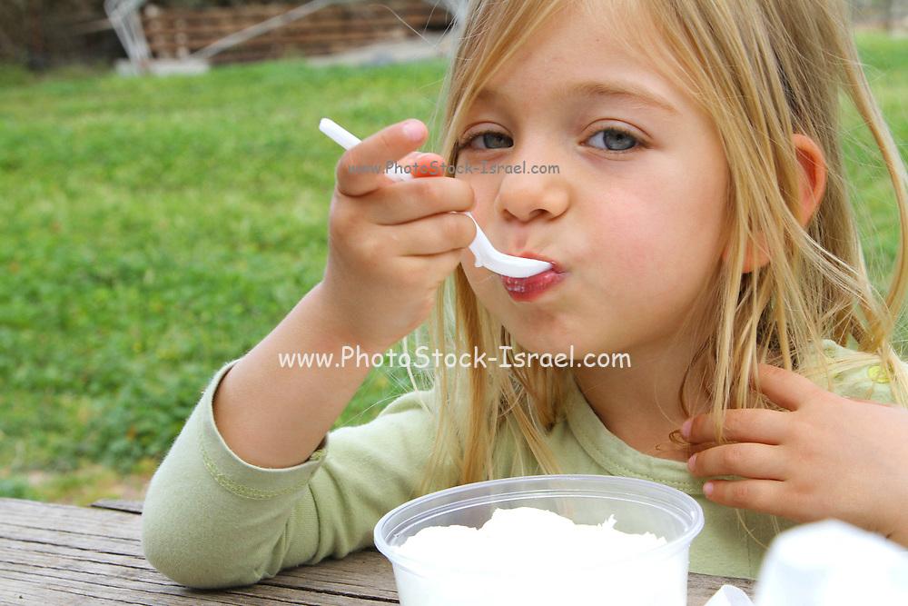 Young Girl eats fresh goat milk yogurt at a dairy farm