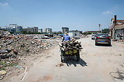 A man rides his rickshaw filled with scrap wood in an area slated for redevelopment in Shanghai, China, on Monday, Aug. 15, 2016.
