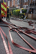 London Fire Brigade (LFB) firefighters attend a local minor roof fire in Herne Hill, Lambeth. Hoses are spread across the road, a street in a residential area of south London as firemen work towards putting out this small fire house.