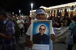 A man poses for a picture while holding a poster of Saint Oscar Arnulfo Romero.