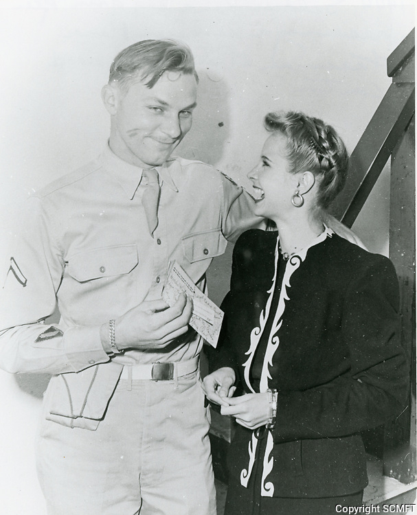 1944 Mona Freeman laughs after giving this soldier a kiss on his cheek at the Hollywood Canteen