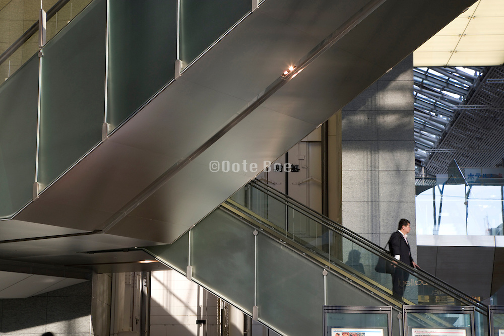 middle aged businessman going down the escalator in the atrium of an modern office building