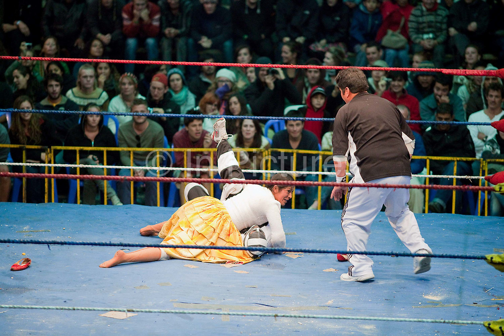Female wrestler pinning male wrestler on floor with referee counting. Lucha Libre wrestling origniated in Mexico, but is popular in other latin Amercian countries, including in La Paz / El Alto, Bolivia. Male and female fighters participate in the theatrical staged fights to an adoring crowd of locals and foreigners alike.