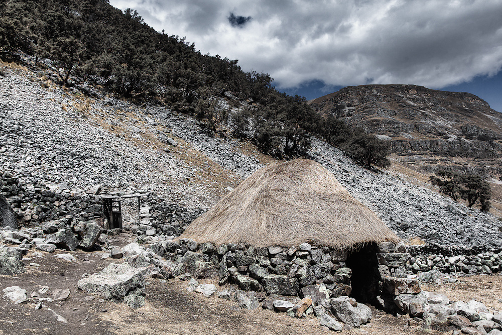 A traditional stone house still in use today with a grass roof and stone walls surrounding the land of a local Peruvian of the Cordillera Huayhuash in the Andes Mountains.