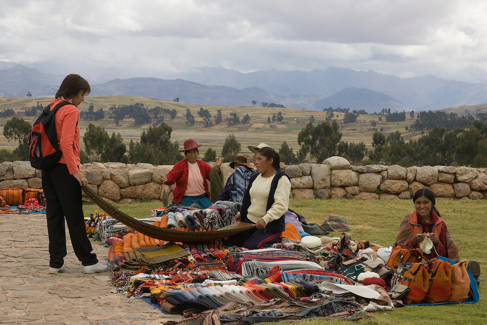 Tourist examines blanket for sale at rural market in Chinchero (near Cuzco), Peru, South America