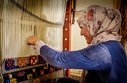 A woman in traditional dress sits weaving carpets in Tazenakht, southern Morocco, Africa<br /> <br /> (c) Andrew Wilson | Edinburgh Elite media