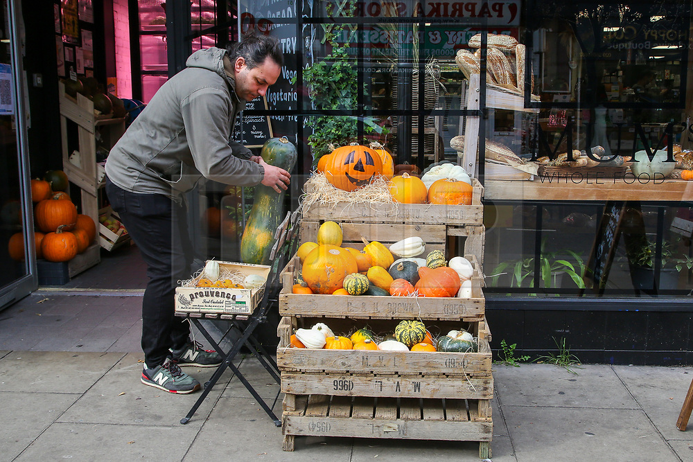 © Licensed to London News Pictures. 12/10/2020. London, UK. A man adds a Naples Long pumpkin to a display of pumpkins outside Mum's Cafe in north London as it prepares for Halloween. The government has announced that trick-and-treating will not be allowed in areas under local lockdown.   <br /> At 3.30pm Prime Minister Boris Johnson will address the House of Commons followed by an address to the public on TV at 6pm where he will outline the three-tier plan with areas in England labelled as medium, high or very high risk, and this will inform the 'appropriate interventions' needed in each area. Photo credit: Dinendra Haria/LNP
