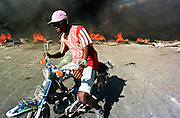 12FEB96-PORT AU PRINCE, HAITI: A man steers a motorcycle around a roadblock of burning tires in the port area of Port-au-Prince, Haiti, Monday, Feb 12, 1996. Haiti had inaugurated a new President, Rene Preval, in Haiti's first peaceful transition of power the week before, when the tumultous term of President Jean Bertrand Aristide came to an end.  PHOTO BY JACK KURTZ