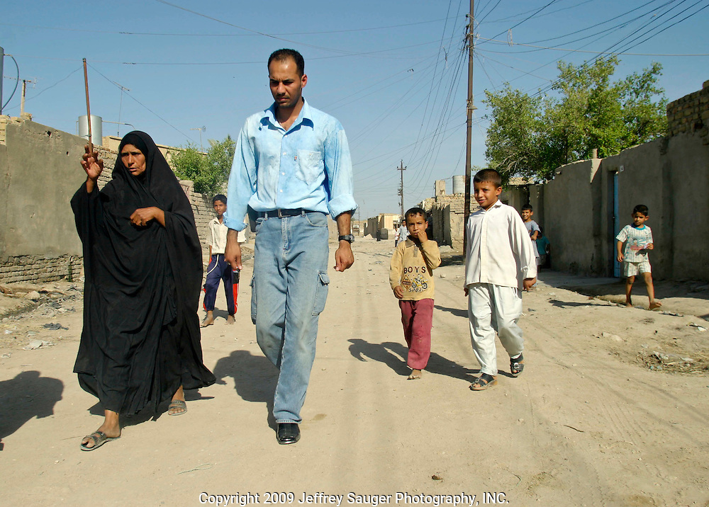 """Emad Al-Kasid, right, walks with Aoum Hussein on the way to her home in the modernized center of the village Suq ash Shuyukh on the outskirts of Nasiriyah, Iraq, Sunday, August 3, 2003. Emad was visiting the neighborhood he grew up in for the first time since 1991. ..He took an indefinate amount of time from his satellite and Arab media company in Dearborn, MI, to come home with his family. On his own, and with his own money he's been meeting with Iraqi businessmen, religious leaders and politicians trying to find ways to bring business and democracy to Iraq. ..""""Can you imagine being away from you home and family for 13 years?"""" he asks. """"I'm torn, do come here to stay and leave all I've built in the U.S.?""""..He is hoping to teach members of his tribe, Al Hacham Al-kasid, and village that there is help available; they just have to ask for it. Another goal of this trip is to see for himself whether Iraq is safe enough for exiles to return and for foreign investment to come in...Since the 1991 uprising against Saddam Hussein in Shiite dominated Southern Iraq, people of this area have suffered greatly through his methods of disrupting daily life. For example, modernization came to a hault as money was diverted to Baath Party strongholds. Check points on on every other corner made it nearly impossible to go to work, the doctor, or visit family. Teachers made $5 U.S. per month and had to spend almost all of their salary for taxis in order to go to work...He tried to kill the people by cutting off the rivers that village survival depends on. Dams and canals dirverted the fresh water from flowing into the swamps by way of tributaries. In effect, without fresh water flowing in, the people started poisoning the water supply themselves by using it to wash and clean. Their primitive sewers still flow freely into the same waters that animals use and that feed their rice fields."""