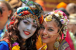 """© Licensed to London News Pictures. 18/06/2017. London, UK. Girls dressed as (L to R) Lord Krishna and consort Radha at the head of the parade.  Devotees celebrate the annual Rathayatra festival (""""cart festival""""), in central London.  Hare Krishna followers towed three huge decorated carts from Hyde Park corner to Trafalgar Square, singing and dancing all the way.  Photo credit : Stephen Chung/LNP"""