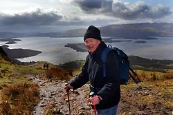 Elderly man exercises by walking in Loch Lomond, Scotland.MODEL RELEASED