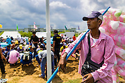 13 MAY 2013 - BANGKOK, THAILAND: A cotton candy vendor works the crowd while Thais looks for blessed rice seeds at the Royal Ploughing Ceremony. After the ceremony, thousands of Thais, mostly family formers, rush onto the ploughed ground to gather up the blessed rice seeds sown by the Brahmin priests. The Royal Plowing Ceremony is held Thailand to mark the traditional beginning of the rice-growing season. The date is usually in May, but is determined by court astrologers and varies year to year. During the ceremony, two sacred oxen are hitched to a wooden plough and plough a small field on Sanam Luang (across from the Grand Palace), while rice seed is sown by court Brahmins. After the ploughing, the oxen are offered plates of food, including rice, corn, green beans, sesame, fresh-cut grass, water and rice whisky. Depending on what the oxen eat, court astrologers and Brahmins make a prediction on whether the coming growing season will be bountiful or not. The ceremony is rooted in Brahman belief, and is held to ensure a good harvest. A similar ceremony is held in Cambodia.    PHOTO BY JACK KURTZ