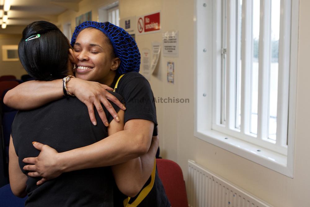 A prisoner hugs her friend during visiting time. HMP Send, closed female prison. Ripley, Surrey.