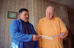 Male client and carer looking at allowances book,