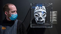 "© Licensed to London News Pictures. 28/07/2020. CITY, UK.  A staff member wearing a facemask next to a mask used for the live visual for ""Mad as Hell"", 2019, by The Chemical Brothers.  Preview of ""Electronic: From Kraftwerk to The Chemical Brothers"" at the Design Museum in Kensington which is reopening after coronavirus lockdown.  The new exhibition explores the hypnotic world of electronic music, from its origins to its futuristic dreams.  The show runs 31 July 2020 – 14 February 2021 with visitors required to adhere to strict social distancing guidelines.  Photo credit: Stephen Chung/LNP"