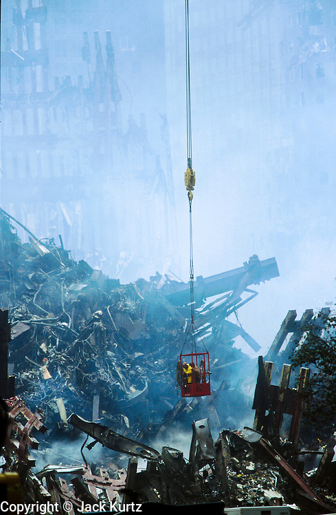 """22 SEPTEMBER 2011 - NEW YORK, NY: With smoke still rising from the rubble, recovery workers work from a bucket hanging from a crane  lift to survey the wreckage of the World Trade Center complex at """"Ground Zero"""" of the WTC terrorist attack, Sept. 22, 2001, eleven days after the attack.  More than 2,900 people were killed when terrorists crashed two airliners into the towers on Sept. 11, 2001.   PHOTO BY JACK KURTZ"""