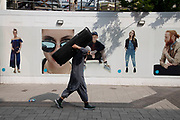 People out shopping walking past a series of posters for Primark depicting other human figures in a strange juxtaposition in Birmingham, United Kingdom.