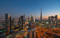 Cityscape view of Burj Khalifa and complex highway interchange and skyscrapers along Sheikh Zayed road in the evening in Dubai, United Arab Emirates, UAE