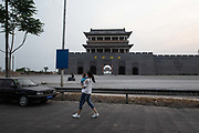 A woman walks past the gates of a baijiu liquor distillery city, made in imitation of a traditional Chinese city,  in Liulin, Shanxi province, China, on Thursday, May 19, 2016. Shanxi is facing a challenge shared by a sweeping region across Chinas industrial north: how to shut down cash-burning mines that employ millions of people whose prospects are uncertain in the new economy promised by President Xi Jinping. New business ventures like the distillery city, funded by coal money with grandiose hopes and expectations, often prove too ambitious and unrealistic.