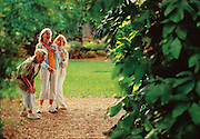 Three women laugh and smile while spending the day inside a botanical garden