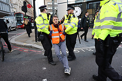 © Licensed to London News Pictures. 25/10/2021. London, UK. Insulate Britain climate change activists being arrested for block traffic on Bishopsgate in the City of London. The group have restarted their actions to block motorways and major roads causing disruption in the week before the COP26 climate meeting in Glasgow on 31/10/2021. Photo credit: Ben Cawthra/LNP