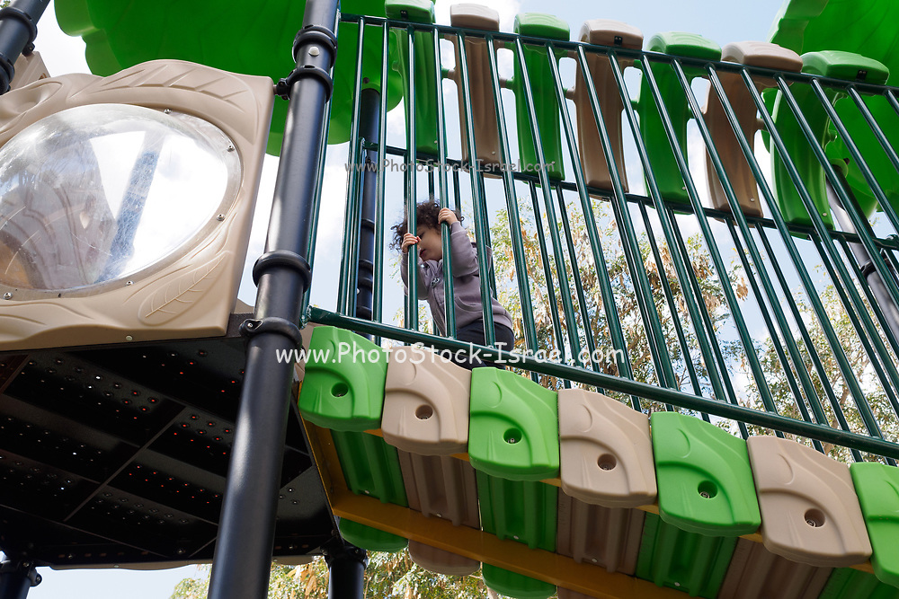 Young toddler girl playing outdoors, in a playground in a park