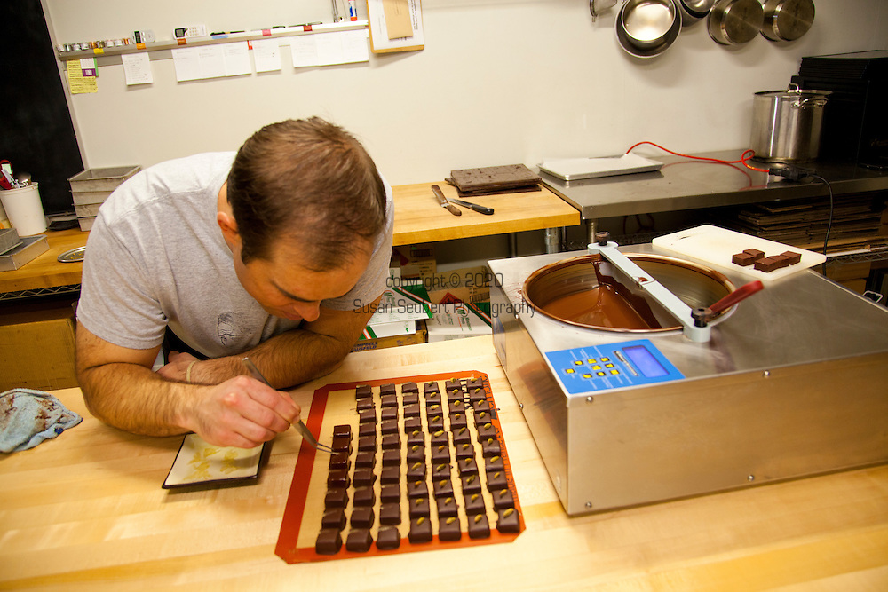 Xocolatl Chocolate owner David Briggs in the kitchen where he makes his small batch, artisan chocolates.  Here David carefully garnishes the pickled watermelon chocolate ganache which will be served at Beaker and Flask's monthly Chocolate Board.