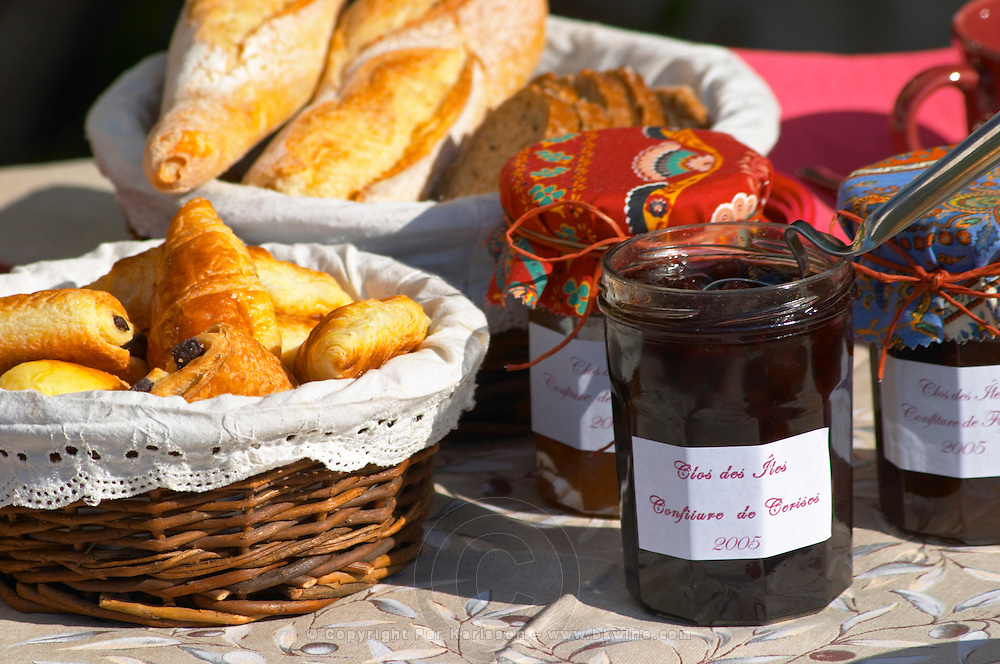 A wicker breakfast basket with croissants, and chocolate breads (pain au chocolat) Jars pots of marmalade jam confiture of fruits and berries covered with colourful Provencal cloth Basket of bread baguette Clos des Iles Le Brusc Six Fours Cote d'Azur Var France