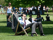 © Licensed to London News Pictures. 22/05/2012. London, UK A man uses a telephone whilst sitting on a deck chair in the sun in Hyde Park.  People enjoy the sunshine in London's Royal Parks today 22 May 2012. Photo credit : Stephen Simpson/LNP