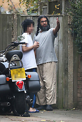 © Licensed to London News Pictures. 13/11/2015. London, UK.  Former Guantanamo detainee Shaker Aamer stands outside his home with an unidentified youth. Shaker Aamer was freed recently after being incarcerated in the US prison located in Cuba since 2002.  Photo credit: Peter Macdiarmid/LNP