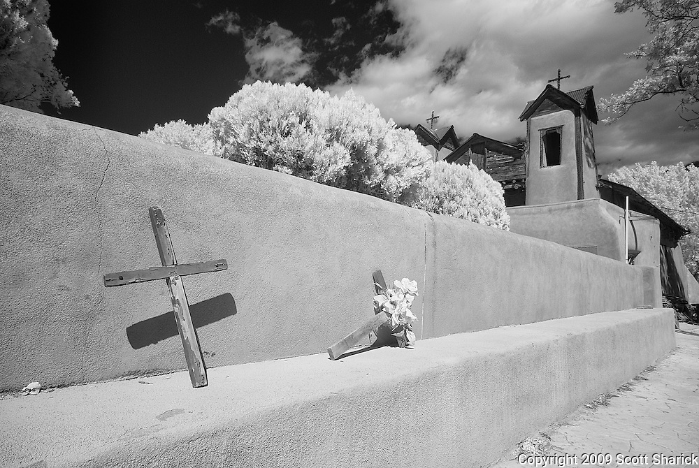 Two crosses lie along the outside wall of the El Santuario de Chimayo, a shrine in the small town of Chimayo, New Mexico.