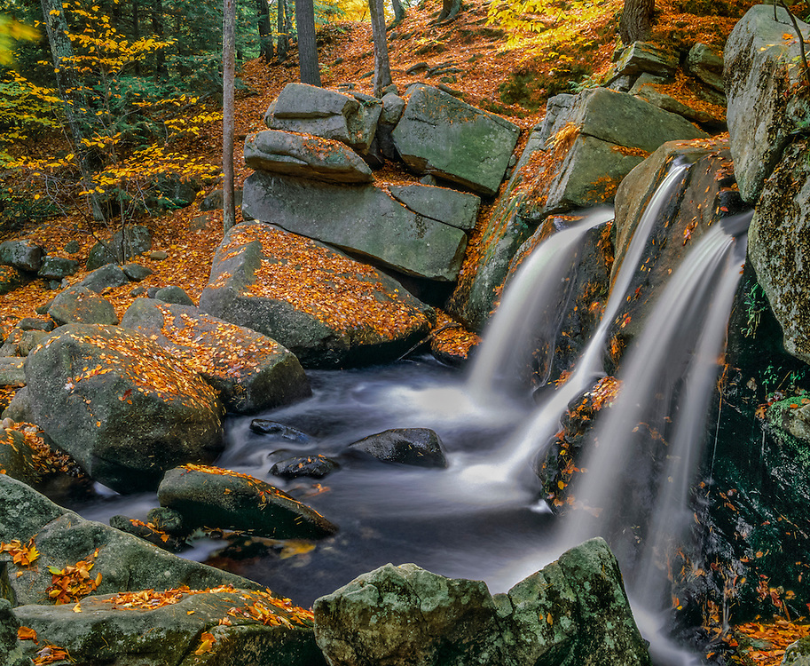 Side view of triple waterfalls, misty water & fall leaves on rocks, Willard Brook State Forest, Ashby, MA