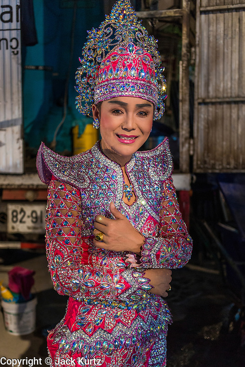 19 JANUARY 2014 - BANGKOK, THAILAND:  A performer in a mor lam show backstage in Khlong Tan Market in Bangkok. Mor Lam is a traditional Lao form of song in Laos and Isan (northeast Thailand). It is sometimes compared to American country music, song usually revolve around unrequited love, mor lam and the complexities of rural life. Mor Lam shows are an important part of festivals and fairs in rural Thailand. Mor lam has become very popular in Isan migrant communities in Bangkok. Once performed by bands and singers, live performances are now spectacles, involving several singers, a dance troupe and comedians. The dancers (or hang khreuang) in particular often wear fancy costumes, and singers go through several costume changes in the course of a performance. Prathom Bunteung Silp is one of the best known Mor Lam troupes in Thailand with more than 250 performers and a total crew of almost 300 people. The troupe has been performing for more 55 years. It forms every August and performs through June then breaks for the rainy season.              PHOTO BY JACK KURTZ