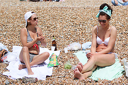 © Licensed to London News Pictures. 29/06/2015. Brighton, UK. hundreds of people take advantage of the start to the expected hottest day of the year so far by relaxing and sunbathing on Brighton beach, today June 29th 2015. Photo credit : Hugo Michiels/LNP