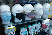 With most shops now open but with retail sales suffering due to the Coronavirus pandemic, face maks for sale on mannequin heads, which became compulsory in shops on the 24th July, go out shopping on Kings Heath High Street on 31st July 2020 in Birmingham, United Kingdom. Coronavirus or Covid-19 is a respiratory illness that has not previously been seen in humans. While much or Europe has been placed into lockdown, the UK government has put in place more stringent rules as part of their long term strategy, and in particular social distancing.