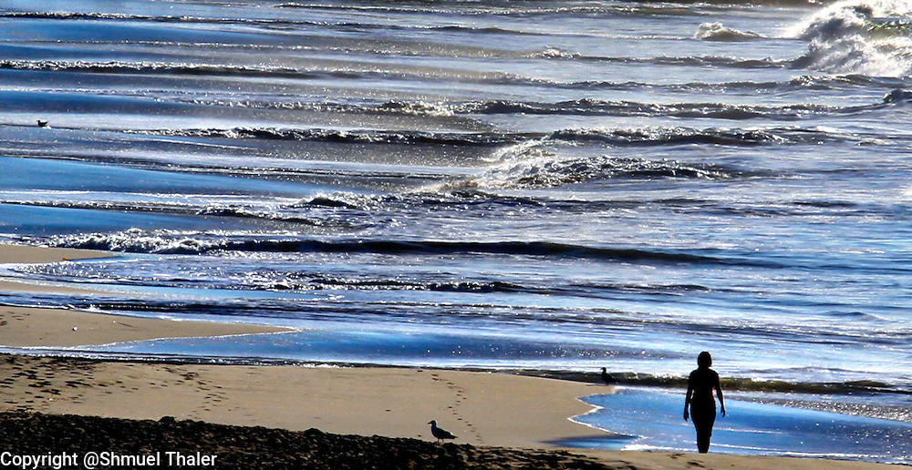 A visitor to Seabright State Beach in Santa Cruz, California walks along the tidal zone on  as the ebb and flow of the tide creates a striking pattern on the shore.<br /> Photo by Shmuel Thaler <br /> shmuel_thaler@yahoo.com www.shmuelthaler.com