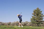 Golfer tees off on desert course
