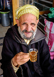 An old Moroccan man in traditional dress with a glass of mint tea outside his shop in the Medina in Marrakech, Morocco, North Africa<br /> <br /> <br /> (c) Andrew Wilson | Edinburgh Elite media