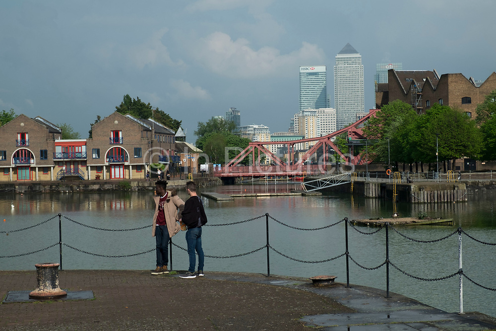 View of the Docklands area, Canary Wharf and financial district through across Shadwell Basin and via the Brunel bridge in Wapping, London, England, United Kingdom.