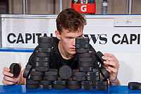 KELOWNA, CANADA - NOVEMBER 14: Braydyn Chizen #22 of the Kelowna Rockets sits on the bench and constructs a puck tower after off-ice pre-game warm up against the Edmonton Oil Kings on November 14, 2017 at Prospera Place in Kelowna, British Columbia, Canada.  (Photo by Marissa Baecker/Shoot the Breeze)  *** Local Caption ***