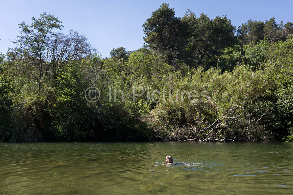 A woman swims in shallow and warm, natural waters of the River Orbieu, on 25th May, 2017, in Ribaute, Languedoc-Rousillon, south of France.