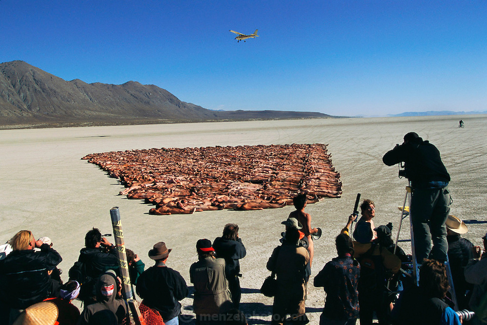 New York artist Spencer Tunick's production of nudes lying on the desert at the Burning Man Festival in the Black Rock Desert, Nevada. Tunick is on a ladder taking photos as a Cessna plane flies overhead. Burning Man is a performance art festival known for art, drugs and sex. It takes place annually in the Black Rock Desert near Gerlach, Nevada, USA.