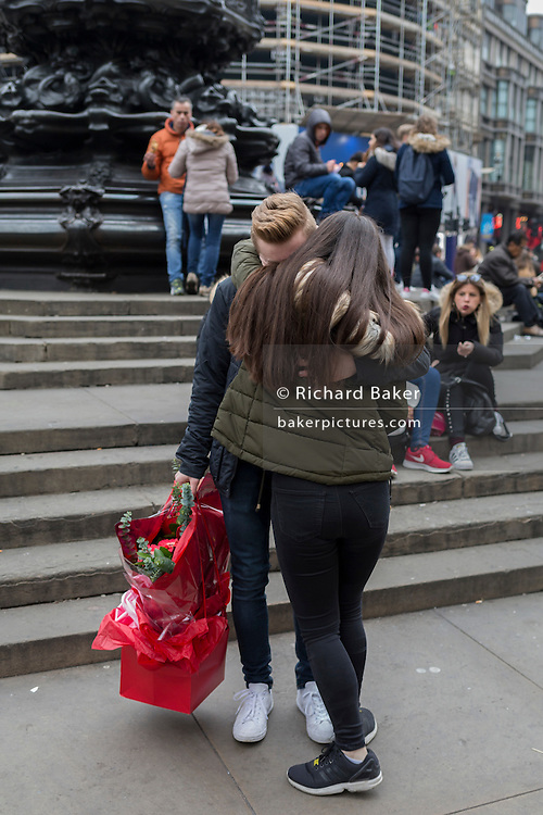 A young man with a bouquet of red roses gets a hug from his girlfriend, on 15th February 2017, in Piccadilly Circus, London borough of Westminster, United Kingdom.