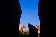 "Downtown and an airplane overhead, seen through Richard Serra's ""Wake"" at the Seattle Art Museum Olympic Sculpture Park in Seattle, Washington."