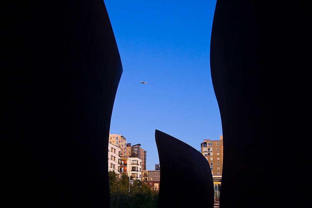"""Downtown and an airplane overhead, seen through Richard Serra's """"Wake"""" at the Seattle Art Museum Olympic Sculpture Park in Seattle, Washington."""