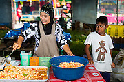 10 JULY 2013 - PATTANI, PATTANI, THAILAND:  A Muslim women sets out mixed seafood salads to sell for Iftar in a market near Krue Se Mosque in Pattani, Thailand. Iftar is the meal Muslims take when they break their daily Ramadan fast. Ramadan is the ninth month of the Islamic calendar, and the month in which Muslims believe the Quran was revealed. Muslims believe that the Quran was sent down during this month, thus being prepared for gradual revelation by Jibraeel (Gabriel) to the prophet Muhammad.  The month is spent fasting during the daylight hours from dawn to sunset. Fasting during the month of Ramadan is one of the Five Pillars of Islam.     PHOTO BY JACK KURTZ