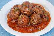 A plate of meatballs with tomato sauce