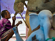 06 SEPTEMBER 2018 - BANGKOK, THAILAND: A craftsman seals the clay on a Ganesh statue at Wat Witsanu Hindu Temple in Bangkok. Indian craftsmen are making statues of the Hindu deity Ganesha for the Ganesh Chaturthi, or Ganesh Festival, held at Hindu temples in September. All of the craftsmen, and the clay they use to fashion the statues, come to Thailand from India every year to make the statues. Although Thais are predominantly Buddhist, the Lord Ganesh, the Hindu overcomer of obstacles, is worshipped by many Thais and Ganesh Chaturthi is celebrated in many Thai communities.    PHOTO BY JACK KURTZ